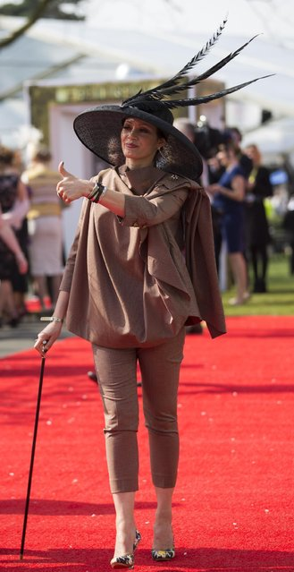 A spectator gives a thumbs up signal during Aintree race meeting's Ladies Day the day before the Grand National horse race at Aintree Racecourse Liverpool, England, Friday, April 10, 2015. (Photo by Jon Super/AP Photo)