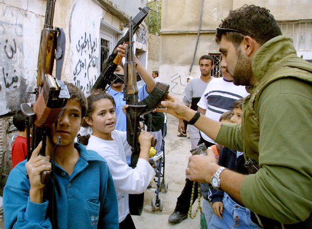 A Palestinian gunman gives his AK-47 assault rifle to a young girl to hold October 26, 2001 in the al-Azzar refugee camp, as he takes a break from fighting with Israeli soldiers in the West Bank town of Bethlehem. (Photo by David Silverman/Getty Images)