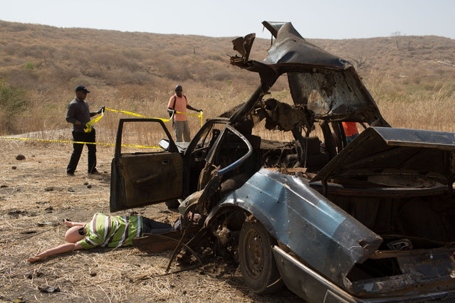 In this photo taken on Thursday, February 18, 2016,  a mannequin is seen outside a vehicles that was exploded during U.S.-led Flintlock military exercises, as students, rear, cordon off the area  in  Thies, Senegal. (Photo by Vincent Tremeau/AP Photo)