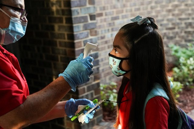 2nd grader Sheilyne has her temperature checked at Benbrook Elementary School on the first day of school amid the coronavirus disease (COVID-19) pandemic in Houston, Texas, U.S., August 23, 2021. (Photo by Go Nakamura/Reuters)