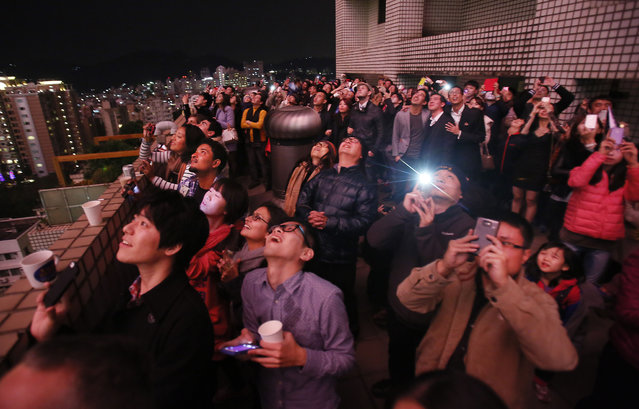 Revelers watch a fireworks display launched from the Taipei101 skyscraper during New Year's Eve celebrations in Taipei, Taiwan, Tuesday, December 31, 2013. (Photo by Wally Santana/AP Photo)
