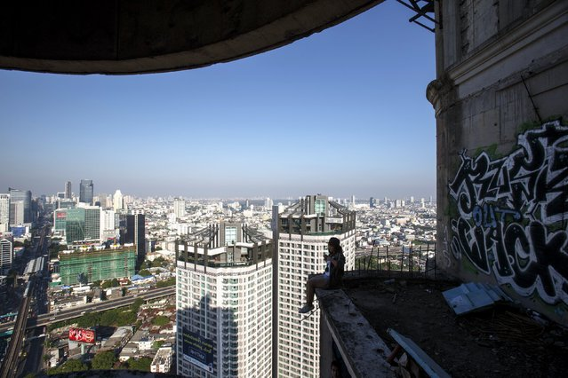 A visitor sits on a balcony of an abandoned building in Bangkok April 19, 2015. (Photo by Athit Perawongmetha/Reuters)