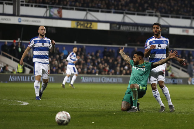 Watford's Andre Gray, second right claims a foul as he falls to the ground when viewing for the ball with Queens Park Rangers' Darnell Furlong during the English FA Cup 5th round soccer match between Queens Park Rangers and Watford at Loftus Road stadium in London, Friday, February 15, 2019. (Photo by Alastair Grant/AP Photo)