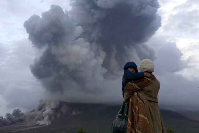 A mother holds her son as they watch the eruption of Mount Sinabung at Berastepu village in Karo district, Indonesia's North Sumatra province, January 10, 2014. More than 22,000 villagers have been evacuated since authorities raised the alert status for Sinabung to the highest level in November 2013, local media reported on Friday. (Photo by Reuters/Beawiharta)