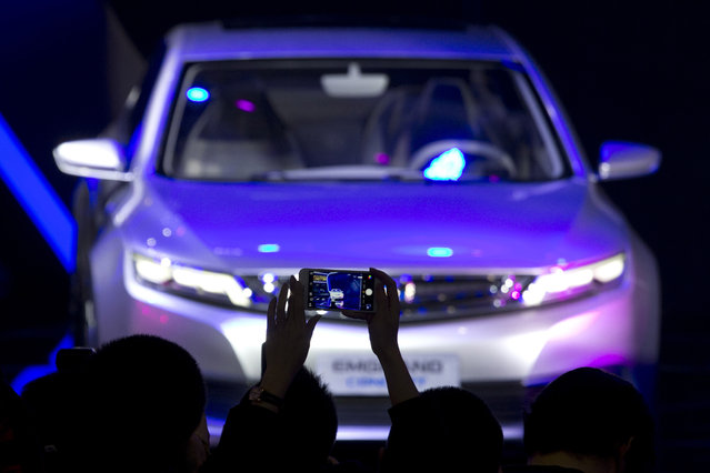 A visitor takes a photo of the Geely Emgrand concept car at the Shanghai Auto Show in Shanghai, Monday, April 20, 2015. (Photo by Ng Han Guan/AP Photo)