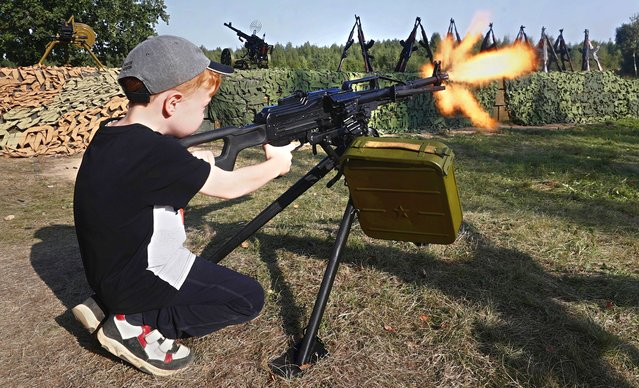 """A boy uses a weapon loaded with blank cartridges as he attends the International Military-Technical Forum """"Army-2021"""" held at Patriot Park in Kubinka, outside Moscow, Russia, 28 August 2021. The 7th International Military-Technical Forum """"Army-2021"""" is held from 23 to 29 August 2021 at Patriot Expo, Kubinka Air Base and Alabino military training grounds. (Photo by Maxim Shipenkov/EPA/EFE)"""