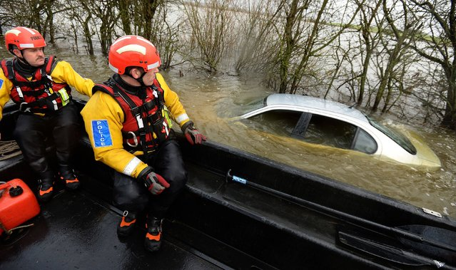 Members of the Avon and Somerset Police Underwater Search Unit inspect a submerged abandoned car as they head to the village of Muchelney in Somerset to offer support to local residents who have been isolated due to the high flood waters in the Somerset Levels since early January. Picture date: Sunday January 26, 2014. (Photo by Andrew Matthews/PA Wire)