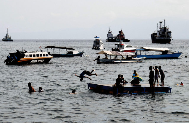 Children jump into the water as they play at the shore of Ternate city, in North Maluku province, on March 8, 2016, one day before a total solar eclipse will occur. The total solar eclipse will occur in several cities in Indonesia on March 9, 2016, one of them being Ternate where more than 3000 tourists have been arriving to the island province to witness the eclipse. (Photo by Bay Ismoyo/AFP Photo)
