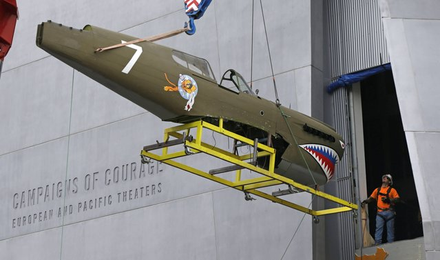 A restored P-40 Curtiss Warhawk fighter plane, one of only 32 known remaining in the world, is hoisted by crane to the second floor for permanent display at the National World War II Museum in New Orleans, Monday, February 3, 2014. The plane, painted in the scheme of the famed Flying Tigers, will be displayed in the museum's new pavilion, Campaigns of Courage: European and Pacific Theaters. (Photo by Gerald Herbert/AP Photo)