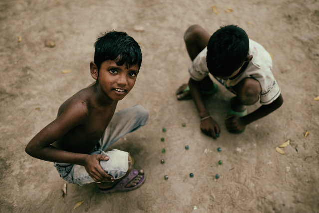 """It's a game we rarely see these days, especially in the west. These two boys were playing marbles in a back street of Kolkata, near the Howrah bridge – and at least one of them was more interested in the game than the man with the camera"". (Photo by Hamish Scott-Brown/The Guardian)"