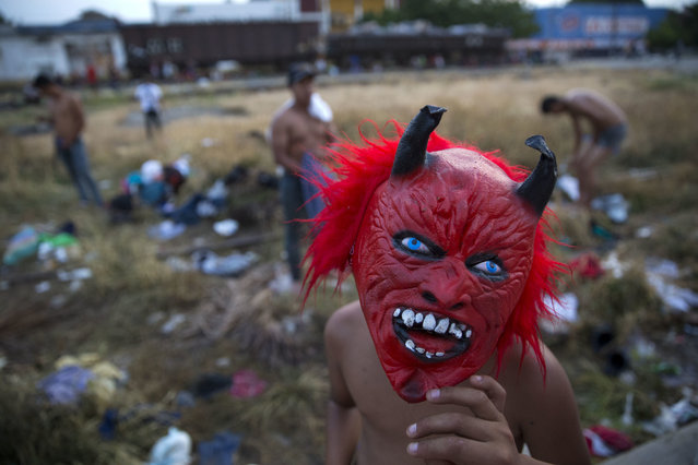 In this October 26, 2018 photo, a boy wears a devil mask he had just bought in a local shop, as the caravan of Central American migrants stops for the night in Arriaga, Mexico. Many migrants said they felt safer traveling and sleeping with several thousand strangers in unknown towns than hiring a smuggler or trying to make the trip alone. (Photo by Rebecca Blackwell/AP Photo)