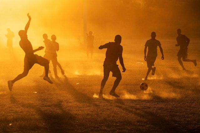 Migrants seeking asylum in the U.S., who returned to the Mexican side of the border to avoid deportation, play soccer in a makeshift migrant camp in Braulio Fernandez Ecological Park in Ciudad Acuna, Mexico, September 22, 2021. (Photo by Go Nakamura/Reuters)