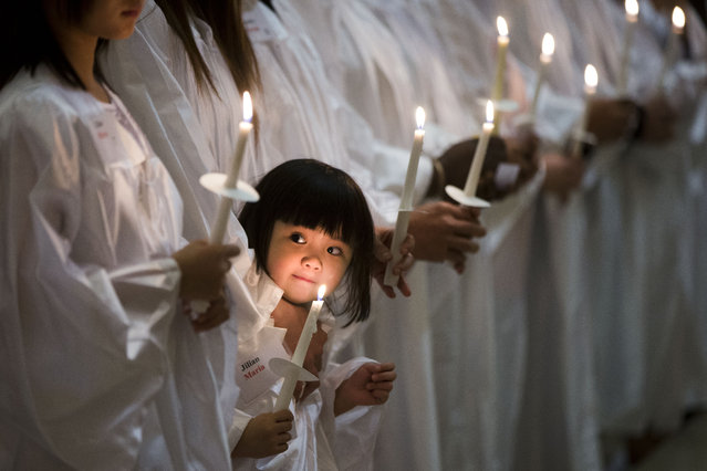 In this Saturday, April 4, 2015 photo, Vietnamese-American Jillian Nguyen, 3, stands with others during their baptism into the Catholic faith, at Saint Helena Catholic Church in Philadelphia. (Photo by Matt Rourke/AP Photo)
