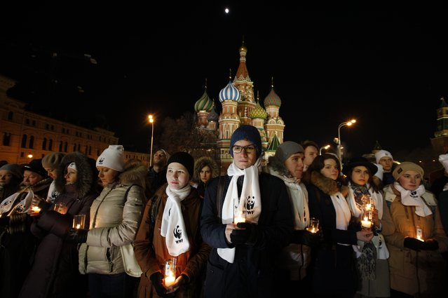 People holding candles prepare to mark Earth Hour in front of St. Basil Cathedral on Red Square in Moscow, Russia, Saturday, March 19, 2016. The participants said they also used the event to pay tributes to the victims of the Dubai plane crash in southern Russia that killed all 62 people aboard on Saturday. (Photo by Alexander Zemlianichenko/AP Photo)