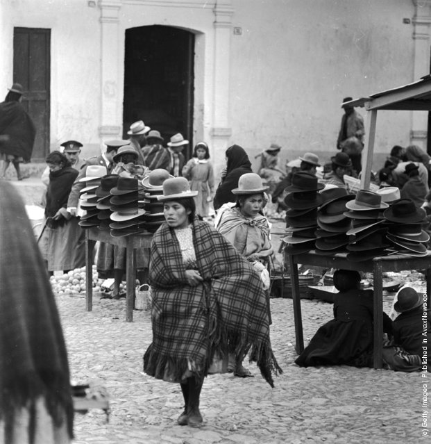 The women of Peru frequently wear masculine-style hats, as seen by the clientele of this hat stall in the marketplace of Puno, in the Peruvian Andes, 1955