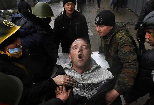 An injured man struggles to breathe as he is carried on a stretcher by anti-government protesters after clashes with riot police in the Independence Square in Kiev February 20, 2014. (Photo by Yannis Behrakis/Reuters)