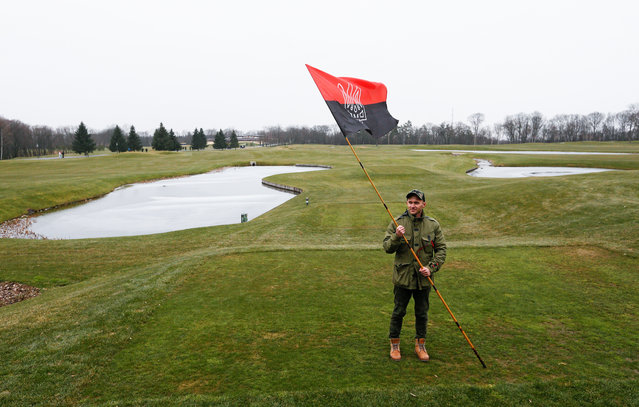 A protester holds an alternative Ukrainian flag on a golf field at the residence of Ukrainian President Viktor Yanukovych in Mezhyhirya village near of Kiev, Ukraine, February 22, 2014. Protesters took full control of the Yanukovych residence and provided free access of the premises for Ukrainian and the media. (Photo by Sergey Dolzhenko/EPA)