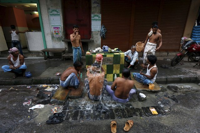 Men bathe at a roadside municipal tap in Kolkata, India, March 12, 2016. Some people in Kolkata earn a living by selling second-hand clothes, driving rickshaws or in the city's food markets. Those too poor to afford a home of their own sleep where they work, helping people who moved to the city to find work to send money back home. Outside working hours residents of the city formerly called Calcutta might enjoy a game of chess or carrom, while children play soccer with friends. (Photo by Rupak De Chowdhuri/Reuters)