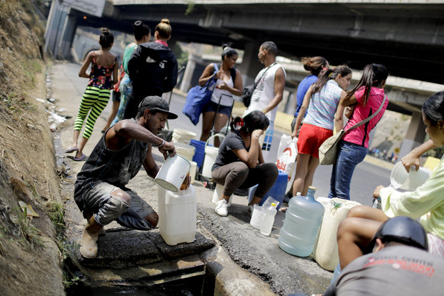 Residents collect water from a ditch next to a highway in Caracas, Venezuela, Tuesday, April 2, 2019. Since a massive power failure struck on March 7, the nation has experienced near-daily blackouts and a breakdown in critical services such as running water and public transportation. (Photo by Natacha Pisarenko/AP Photo)