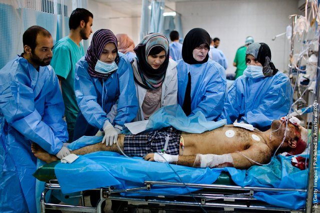 Medical staff treat a Libyan rebel fighter after a bullet entered one ear and exited out the other, according to a doctor, at the Tripoli Central Hospital