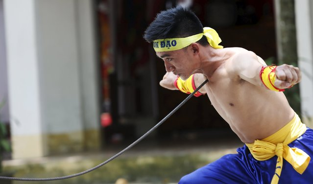Vietnamese student Le Duc Thang, 24, bends a metal spear by pressing it into his throat as he performs during a showcase of traditional Thien Mon Dao kung fu at Du Xa Thuong village, southeast of Hanoi, Vietnam May 10, 2015. (Photo by Reuters/Kham)
