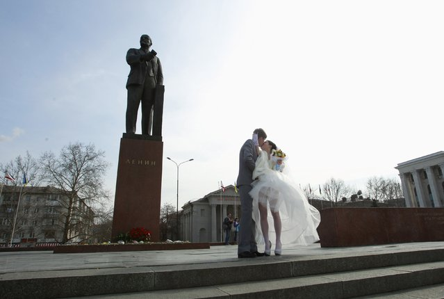 A newly-wed couple kiss near a statue of Lenin in the Crimean city of Simferopol March 1, 2014. The International airport at Simferopol, the main city in Ukraine's Crimea region, said on Saturday its airspace was closed and there were no flights to or from the airport. (Photo by David Mdzinarishvili/Reuters)