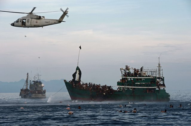 Rohingya migrants swim to collect food supplies dropped by a Thai army helicopter after they jumped from a boat (R) drifting in Thai waters off the southern island of Koh Lipe in the Andaman sea on May 14, 2015. (Photo by Christophe Archambault/AFP Photo)