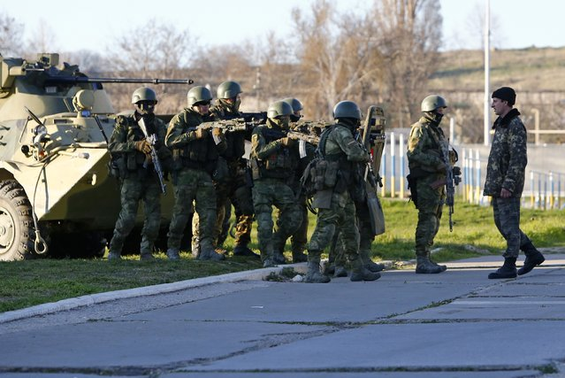 A Ukrainian serviceman (R) talks to armed men, believed to be Russian servicemen, who stand guard at a military airbase, in the Crimean town of Belbek near Sevastopol March 22, 2014. (Photo by Shamil Zhumatov/Reuters)