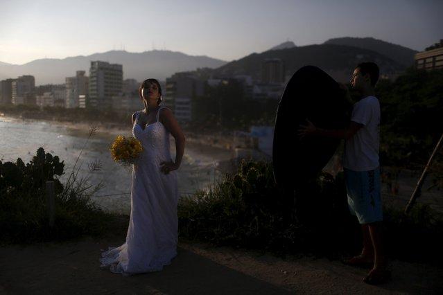 A bride poses for her photographer at the Arpoador beach in Rio de Janeiro, Brazil April 10, 2016. (Photo by Pilar Olivares/Reuters)