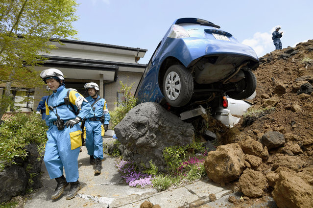 Police officers conduct a search operation at the site of a landslide caused by an earthquake in Minamiaso, Kumamoto prefecture, Japan, Sunday, April 17, 2016. Two nights of increasingly terrifying earthquakes flattened houses and triggered major landslides in southern Japan. (Photo by Yohei Fukai/Kyodo News via AP Photo)