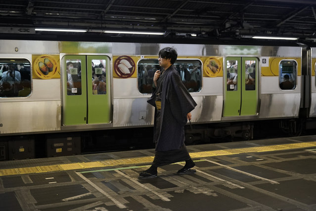 In this Saturday, May 25, 2019, photo, a young man wearing a traditional kimono walks past a packed Yamanote Line train at Shinjuku Station in Tokyo. Operated by the East Japan Railway Co., the Yamanote Line in Tokyo makes a loop around the center of the city, connecting 29 stations that include key stops such as Shinjuku, Shibuya and Ikebukuro. A complete loop of about an hour offers scenes of Japanese daily lives. (Photo by Jae C. Hong/AP Photo)