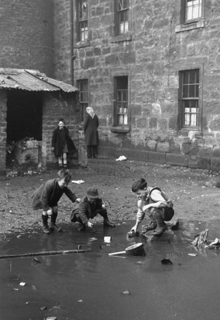Boys play in a puddle in the slums of Gorbals, Glasgow on January 31, 1948. (Photo by Bert Hardy/Picture Post/Getty Images)
