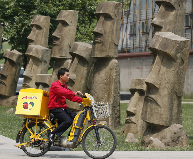 Replicas of the Moai statues on Easter Island, at a business district in Beijing, May 22, 2013. (Photo by Kim Kyung-Hoon/Reuters)