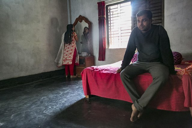 Meghla does her makeup while her husband Liton sits on the bed on March 7, 2017 in Khulna division, Bangladesh. (Photo by Allison Joyce/Getty Images)