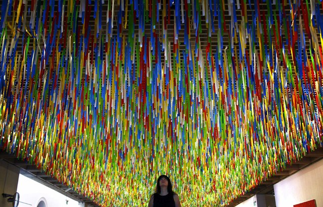 """Australian artist Nike Savvas inspects her artwork titled """"Rally"""" that hangs from the roof of the New South Wales Art Gallery April 7, 2014. Savvas says her hanging installation, which is made up of more than 60,000 colored ribbons being blown by fans, was inspired by her recent visit to Brazil and represents """"fields of color in motion that swirls and regathers like an unpredictable crowd"""". (Photo by David Gray/Reuters)"""