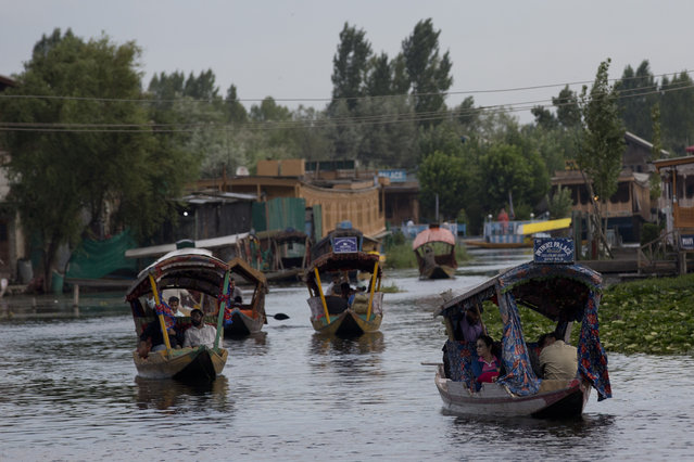 """Tourists in Shikaras, a traditional gondola, cross the Dal Lake as they prepare to leave Srinagar, Indian controlled Kashmir, Saturday, August 3, 2019. A government order in Indian-administered Kashmir on Friday asked tourists and Hindu pilgrims visiting a Himalayan cave shrine """"to curtail their stay"""" in the disputed territory, citing security concerns and intensifying tensions following India's announcement it was sending more troops to the region. (Photo by Dar Yasin/AP Photo)"""