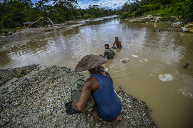 Men work at Nacupay gold mine on the bank of a river in El Callao, Bolivar state, southeastern Venezuela on February 24, 2017. (Photo by Juan Barreto/AFP Photo)