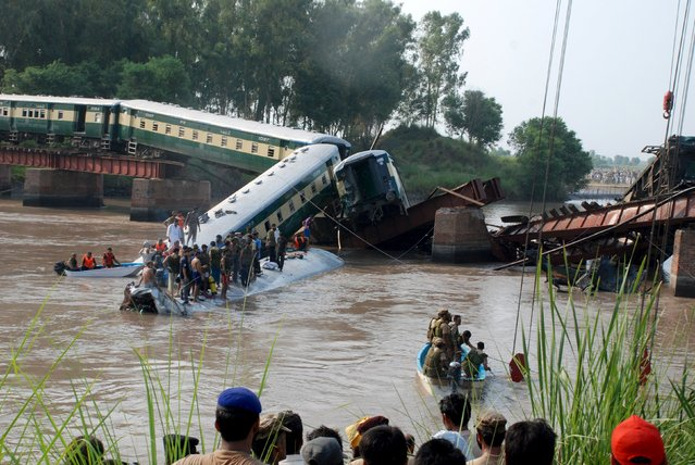 Pakistan Army soldiers and rescue workers gather at the site after a train fell in a canal, near Gujranwala, Pakistan, July 2, 2015. A train carrying hundreds of Pakistan military personnel and their families plunged into a canal on Thursday, killing 12 soldiers, when a bridge collapsed in what the army suspects was sabotage, officials said. (Photo by Reuters/Stringer)