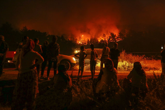 Flames and smoke rising after a fire that broke out in Izmir province of Aegean Turkey on August 19, 2019. Fire brigade crew continue their works. Forest fires have consumed some 500 hectares (over 1,200 acres) of land in Izmir, Turkeys Aegean coast. On Sunday, the fires broke out in four different regions – including two in the southwestern Mugla province and others in Izmir province, according to Agriculture and Forest Ministry. (Photo by Emin Menguarslan/Anadolu Agency via Getty Images)