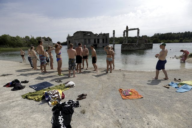 People get ready to swim near Murru prison, an abandoned Soviet prison, in Rummu quarry, Estonia, during hot weather July 4, 2015. (Photo by Ints Kalnins/Reuters)