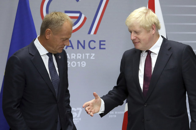 Britain's Prime Minister Boris Johnson, right, reaches out to shakes hands with President of the European Council Donald Tusk before a meeting on the side of the G-7 summit in Biarritz, France Sunday, August 25, 2019. (Photo by Markus Schreiber/AP Photo)