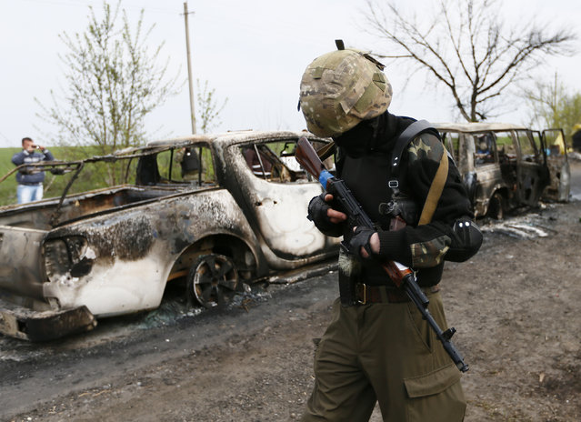 A Pro-Russian militant walks past burnt cars near a checkpoint that was the scene of a gunfight overnight near the city of Slaviansk, April 20, 2014. At least two people were killed in a gunfight early on Sunday near a Ukrainian city controlled by pro-Russian separatists, testing an already fragile international accord that is supposed to defuse Ukraine's armed stand-off. (Photo by Gleb Garanich/Reuters)