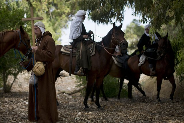 In this Friday, July 3, 2015 photo, Israeli and Russian members of knight clubs get on their horses before marching 27 kilometers (17 miles) to the reenactment of the Battle of Hattin from the ancient northern city of Zippori to Horns of Hattin, northern Israel. (Photo by Oded Balilty/AP Photo)