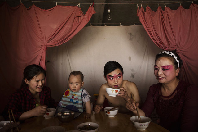 Members of the Jinyuan Opera Company have lunch during a break in the performance at the Dongyue Temple on May 2, 2016 in Cangshan, Sichuan province, China. (Photo by Kevin Frayer/Getty Images)