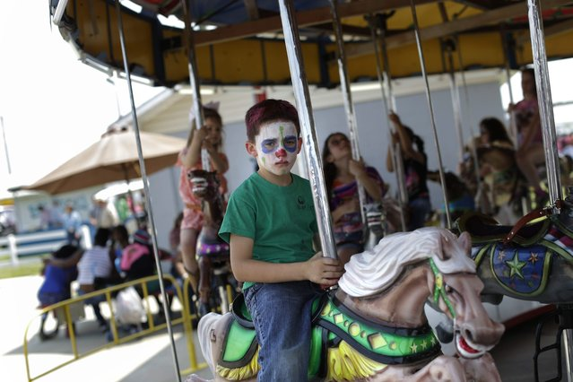 A boy with a painted face rides on a merry-go-round at the Angola Prison Rodeo in Angola, La., Saturday, April 26, 2014. The rodeo got its start in 1965 at a small arena built by a handful of inmates and prison personnel, but it wasn't until 1967 that the rodeo opened to the public. (Photo by Gerald Herbert/AP Photo)