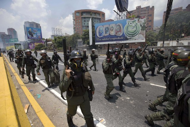 Bolivarian National Guard officers advance towards demonstrators during a protest in Caracas, Venezuela, Monday, April 10, 2017. (Photo by Ariana Cubillos/AP Photo)
