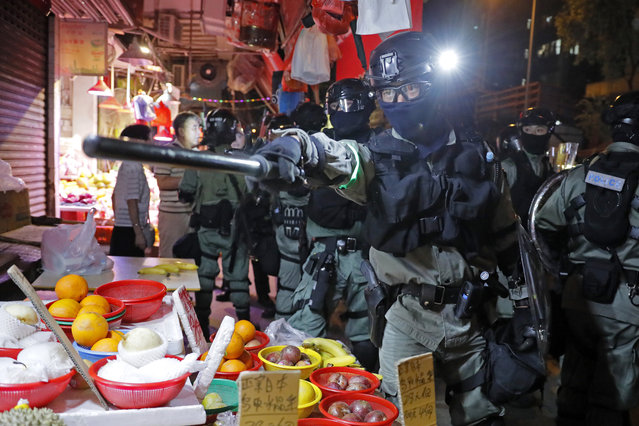 Police arrive after pro-China supporters confront with journalists in north point, at a local market of Hong Kong, Sunday, September 15, 2019. Police fired a water cannon and tear gas at protesters who lobbed Molotov cocktails outside the Hong Kong government office complex Sunday, as violence flared anew after thousands of pro-democracy supporters marched through downtown in defiance of a police ban. (Photo by Kin Cheung/AP Photo)