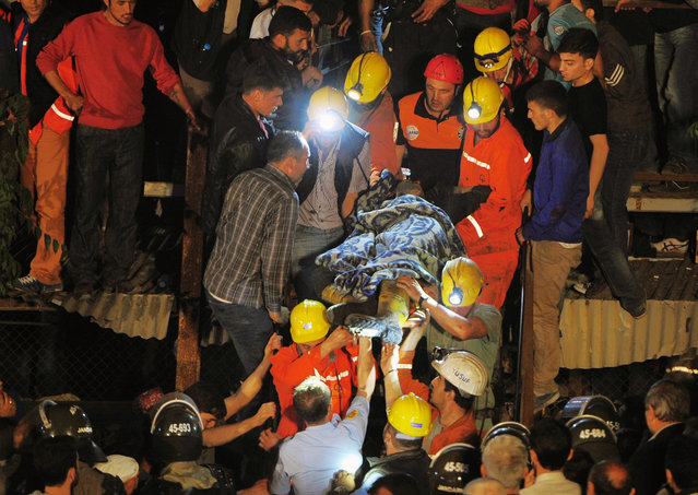 Miners carry a rescued friend hours after an explosion and fire at a coal mine killed at least 17 miners and left up to 300 workers trapped underground, in Soma, in western Turkey, late Tuesday, May 13, 2014, a Turkish official said. Twenty people were rescued from the mine but one later died in the hospital, Soma administrator Mehmet Bahattin Atci told reporters. The town is 250 kilometers (155 miles) south of Istanbul. The death toll was expected to rise. (Photo by AP Photo)