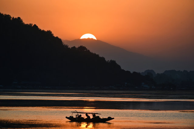 Fishermen wait on a small boat after casting their net at Dal Lake during sunset in Srinagar on September 9, 2019. (Photo by Tauseef Mustafa/AFP Photo)