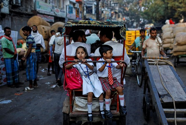 School children ride in a cycle rickshaw through a market in the old quarters of Delhi, India, October 10, 2019. (Photo by Danish Siddiqui/Reuters)